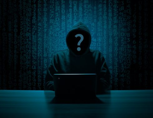 Nondescript hacker sitting in front of a laptop in a dark room